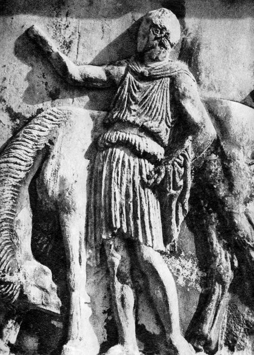 Всадник с конем из торжественного панафенайского сопровождения. Деталь западного фриза Парфенона на Афинском Акрополе. Около 440 г. до н. э. Юноша одет в короткий хитон до колен, который дополняет хламис, скрепленный спереди под горлом застежкой, перекинутый назад и ниспадающий складками вниз по спине, один конец которого переброшен у юноши через руку