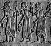 Барельеф с Черного обелиска короля Салманасара, IX век до н. э. Нимруд. Британский музей, Лондон. Мужчины одеты в длинные плащи, украшенные по краям бахромой, а на головах у них мягкие конические шапки с загнутым верхом