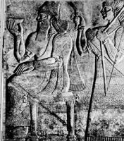Король Ашшурнасирпал. Барельеф из тронного зала Северо-западного дворца, IX век до н. э. Нимруд. Британский музей, Лондон. Церемониальный костюм состоит из королевской тиары с инфулеми (подвесками, спадающими на плечи), длинной туники, плаща, украшенного бахромой, и, наконец, сандалей, подметки которых прикреплены к ноге двумя ремешками.